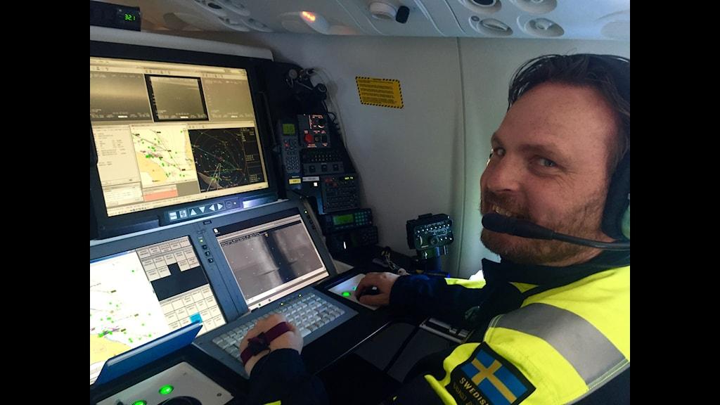 Linus från Kustbevakningen ser på flygplanets bilder över båtar på Medelhavet.