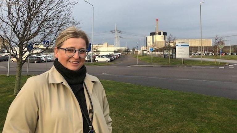 Kvinna framför kärnkraftverk.