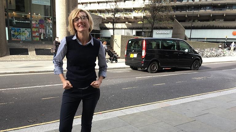 En kvinna står på en gata i London.