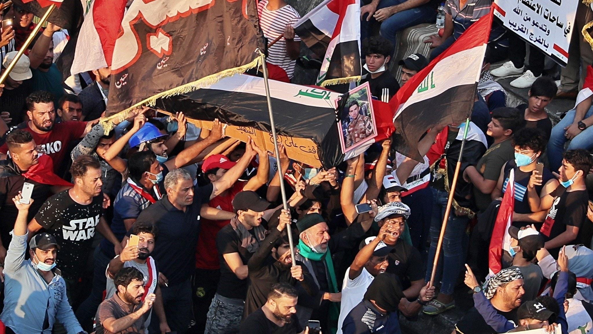Sörjande och protesterande som bär en kista på väg till en begravning i Bagdad, Irak.