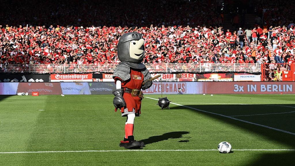 FC Unions maskot på fotbollsplanen inför fullsatta läktare.