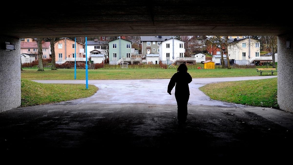 Silluett av en person i gångtunnel på väg mot område med mindre flerfamiljshus eller villor.