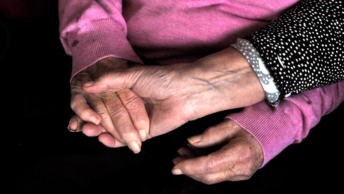 Kvinna håller en äldre kvinnas händer. Hasse Holmberg / TT