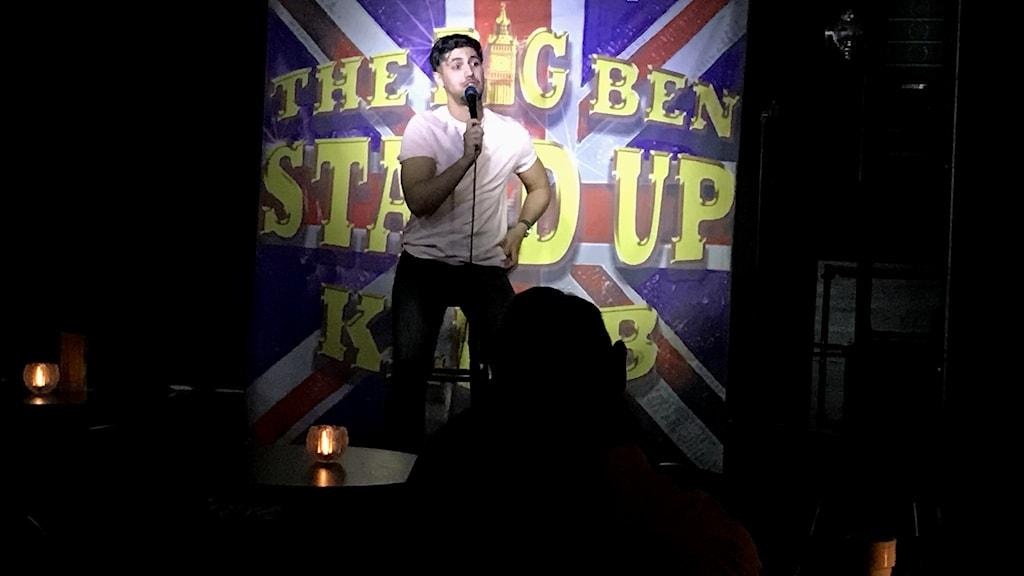 Komikern Ali Gorgi på scen.