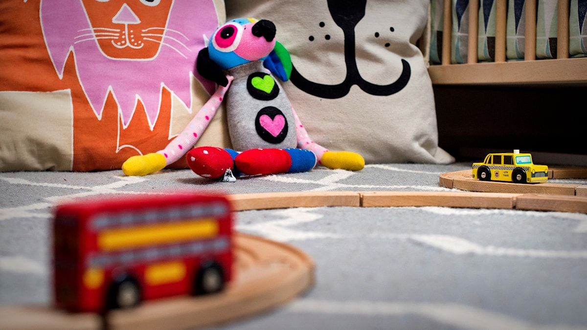 Leksaker på ett golv i ett barnrum.