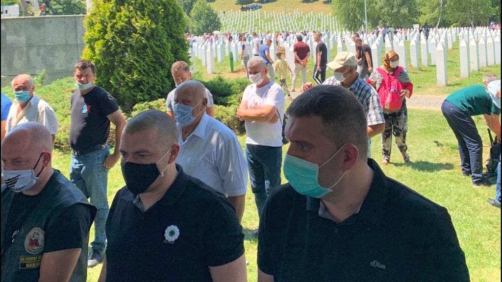 Människor bär mask under minnesstunden i Srebrenica. Arrangörerna följer coronarestriktionerna i Bosnien under minnesdagen.