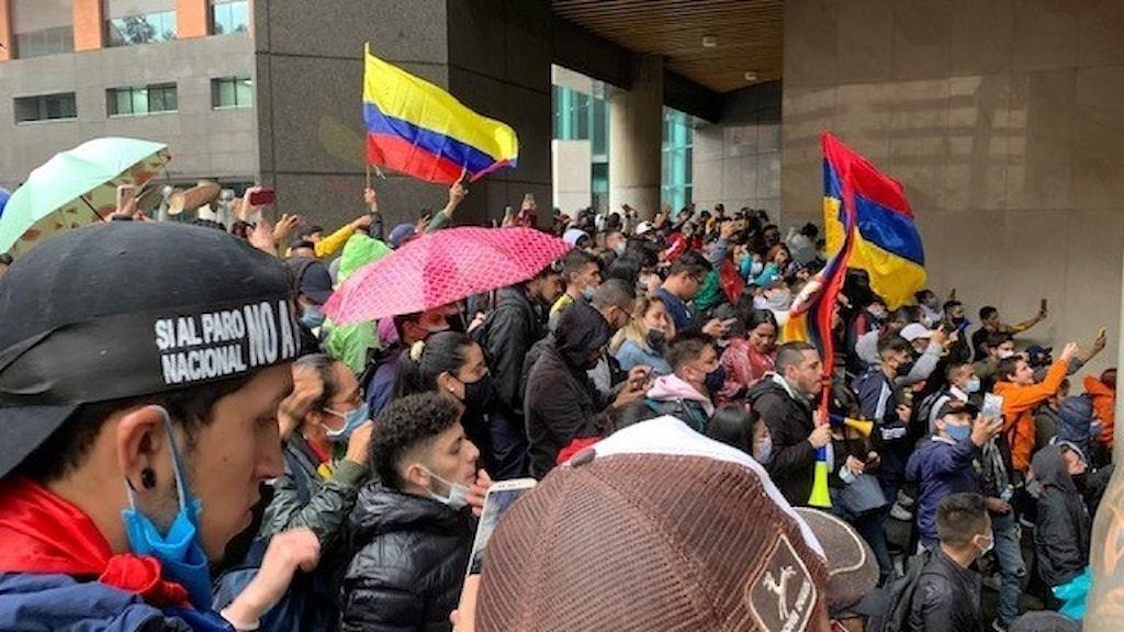Personer som demonstrerar. Colombianska flaggor i luften.