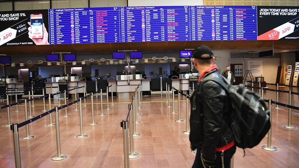 Man med ryggsäck står vid incheckningen på Arlanda flygplats.