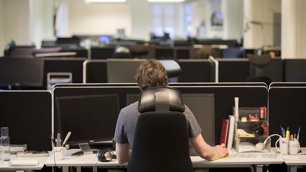 En man fotograferad bakifrån sitter vid sitt skrivbord i ett öppet kontorslandskap.