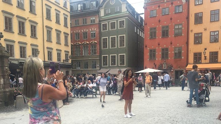 Turister upptagna med sina mobiltelefoner i Gamla stan.