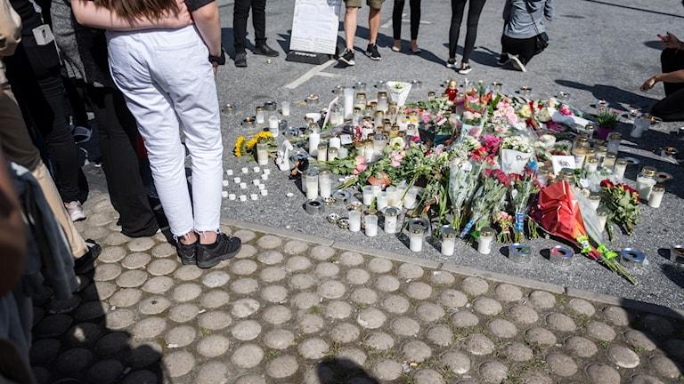 Folk samlas vid blommorna och ljusen på platsen där en tolvårig flicka sköts ihjäl vid en bensinmack i Hallunda i Botkyrka, söder om Stockholm natten mot söndagen.