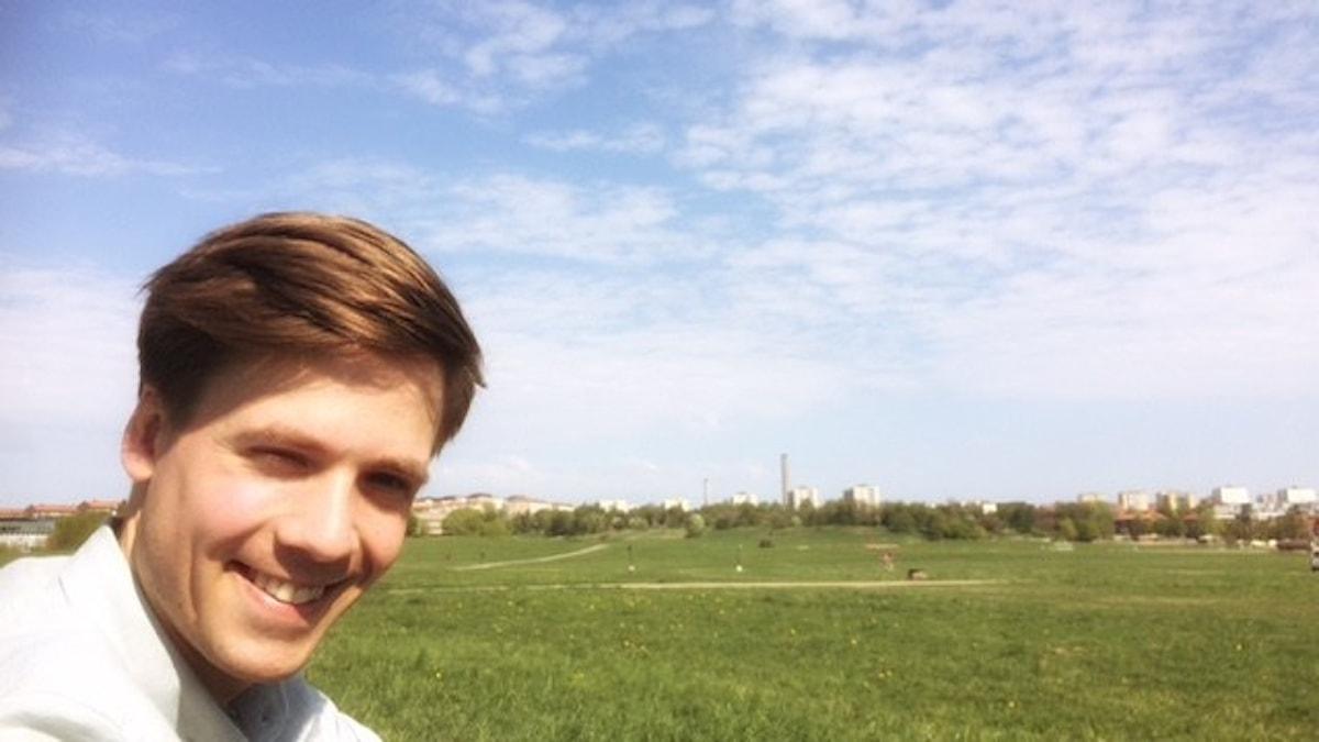 Meteorologen Nils Holmqvist på en solig äng under moln