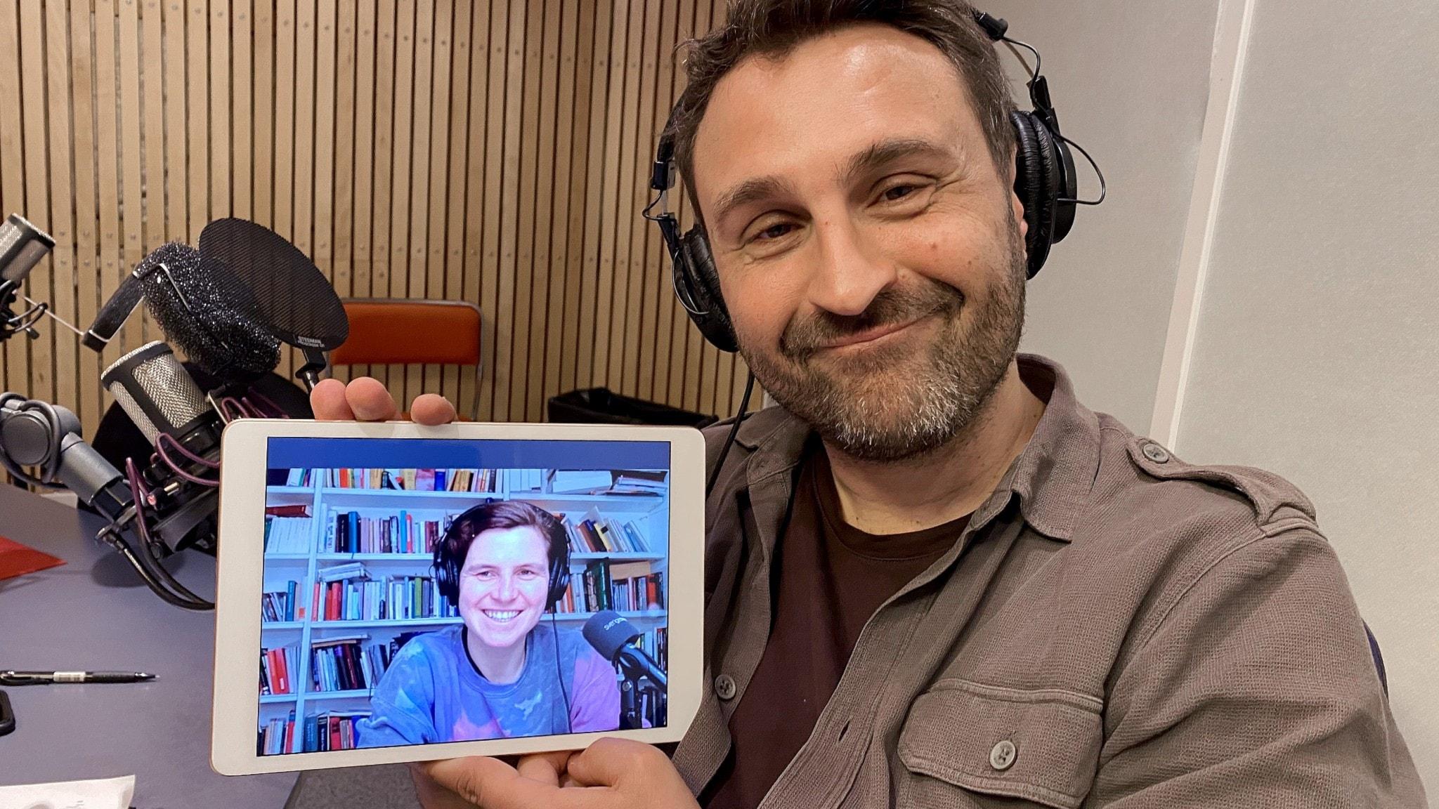 Johar Bendjelloul håller en läsplatta i handen där Judith Schalansky syns på bild uppkopplad från Berlin.