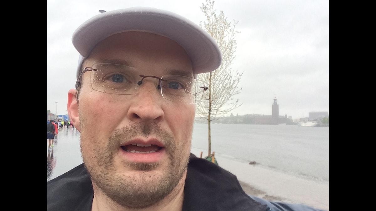 Tuomas Ojala lippalakki päässä ja vesisateessa