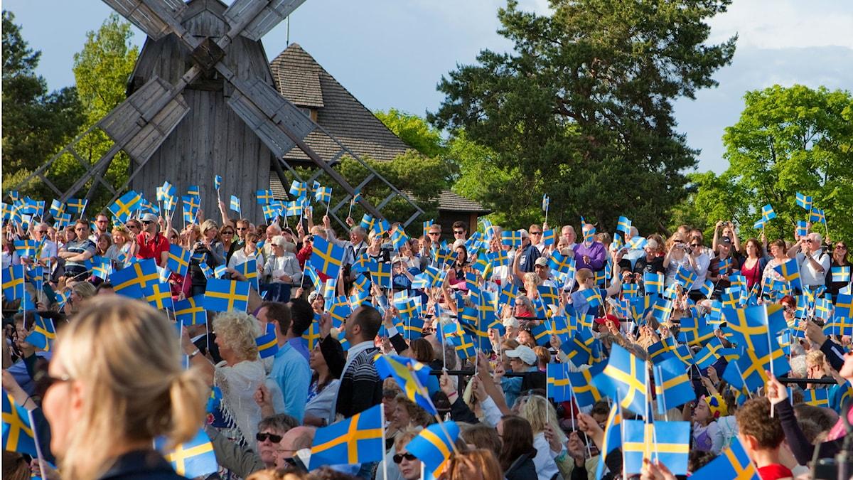 Ruotsinlippuja ja ihmismassaa Skansenilla kauniina kesäpäivänä. Taustalla lehtipuita ja vanha puinen tuulimylly. (Kuvaa rajattu) Kuva: Bengt Nyman / Flickr / (CC BY 2.0)