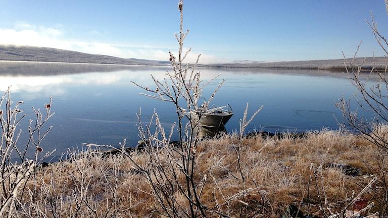 Tunturit heijastuvat peilityyneen järveen ja rannassa on yksinäinen alumiinivene. Rannassa on kuuraa. foto: Erpo Heinolainen SR Sisuradio