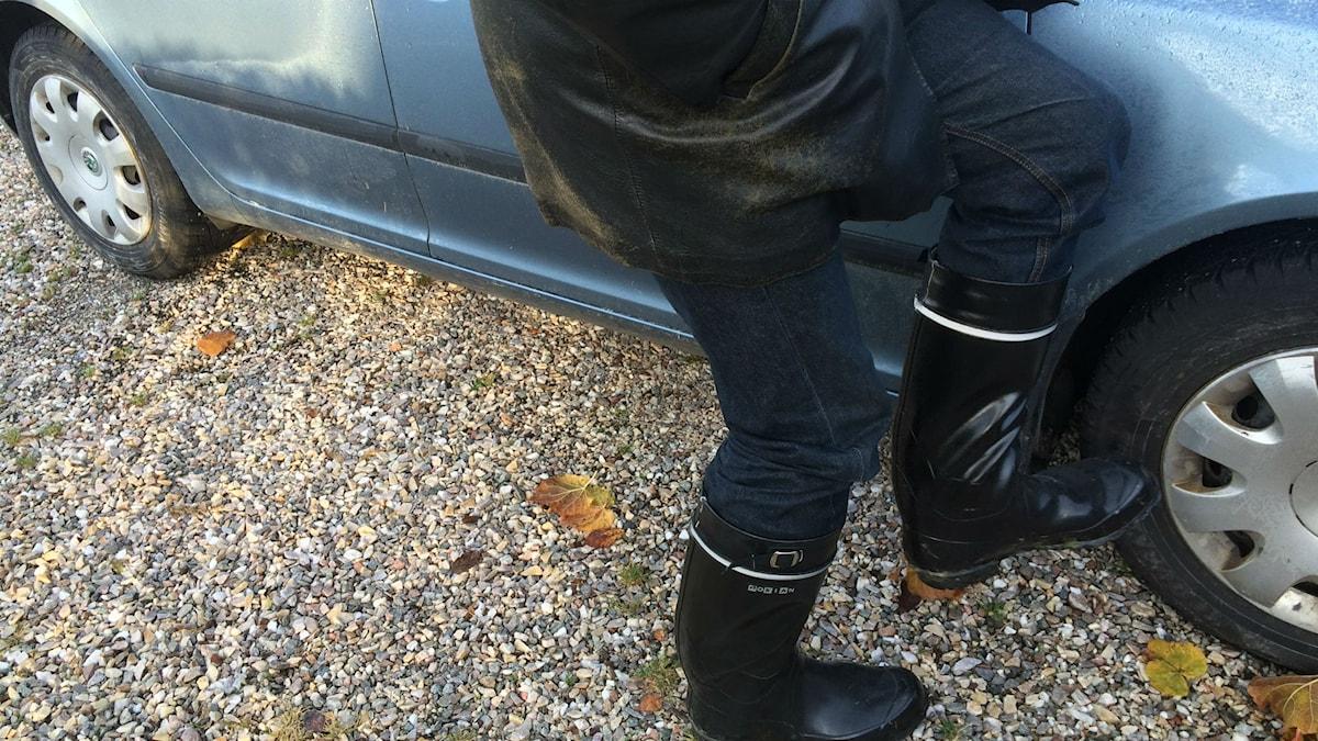 Mies potkii auton rengasta saappaallaan. Kuva:Ulla Rajakisto/Sveriges Radio Sisuradio