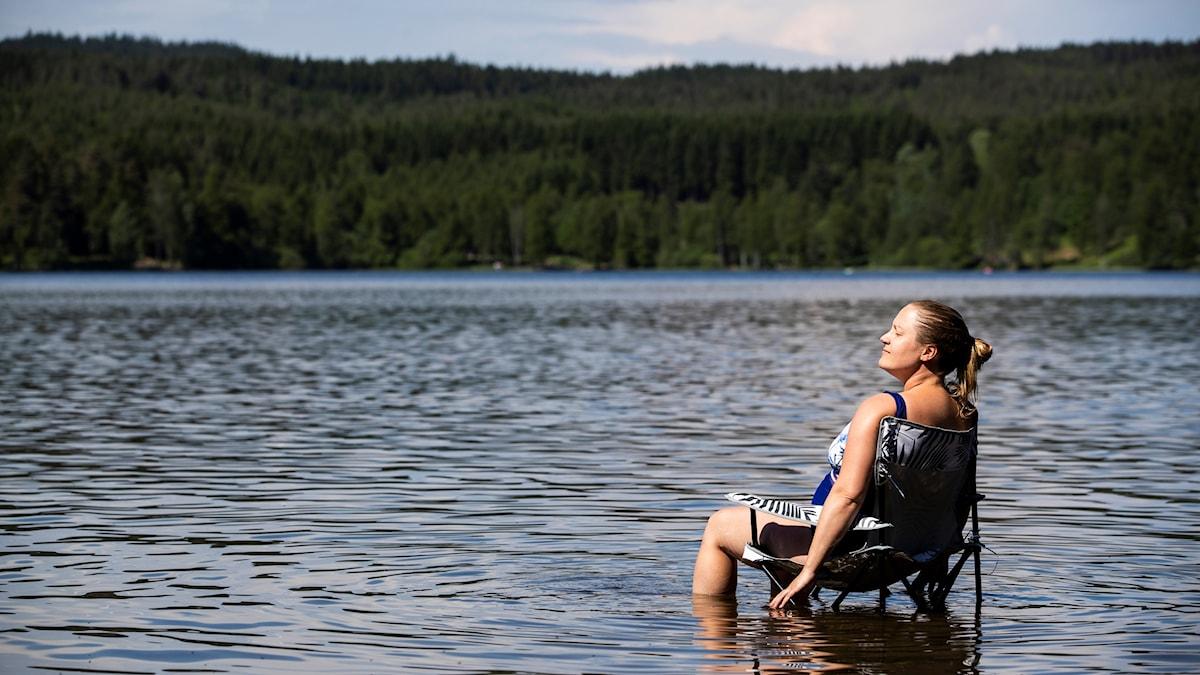 Kvinna sitter på en solstol i vattnet och njuter av solen.