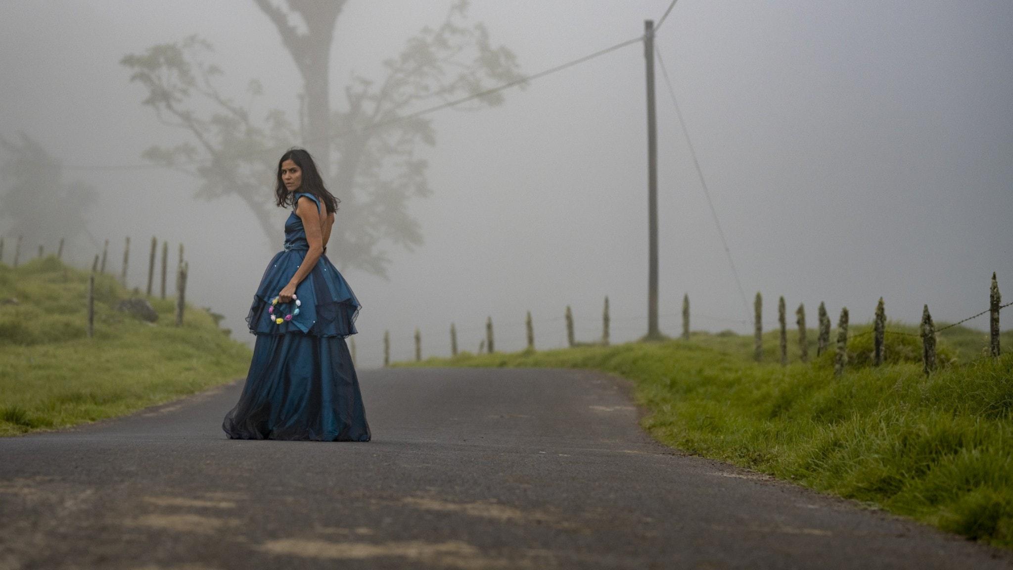 En kvinna står i en fin, blå långklännig på en dimmig landsväg.