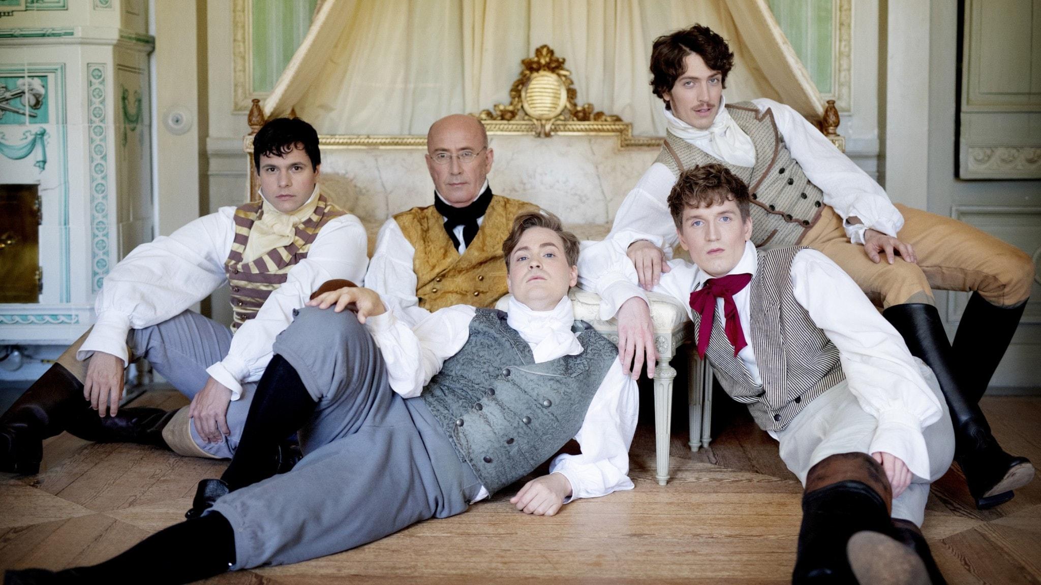 Fem män i 1800tals-kostymer ligger på golvet i en utmanande pose.