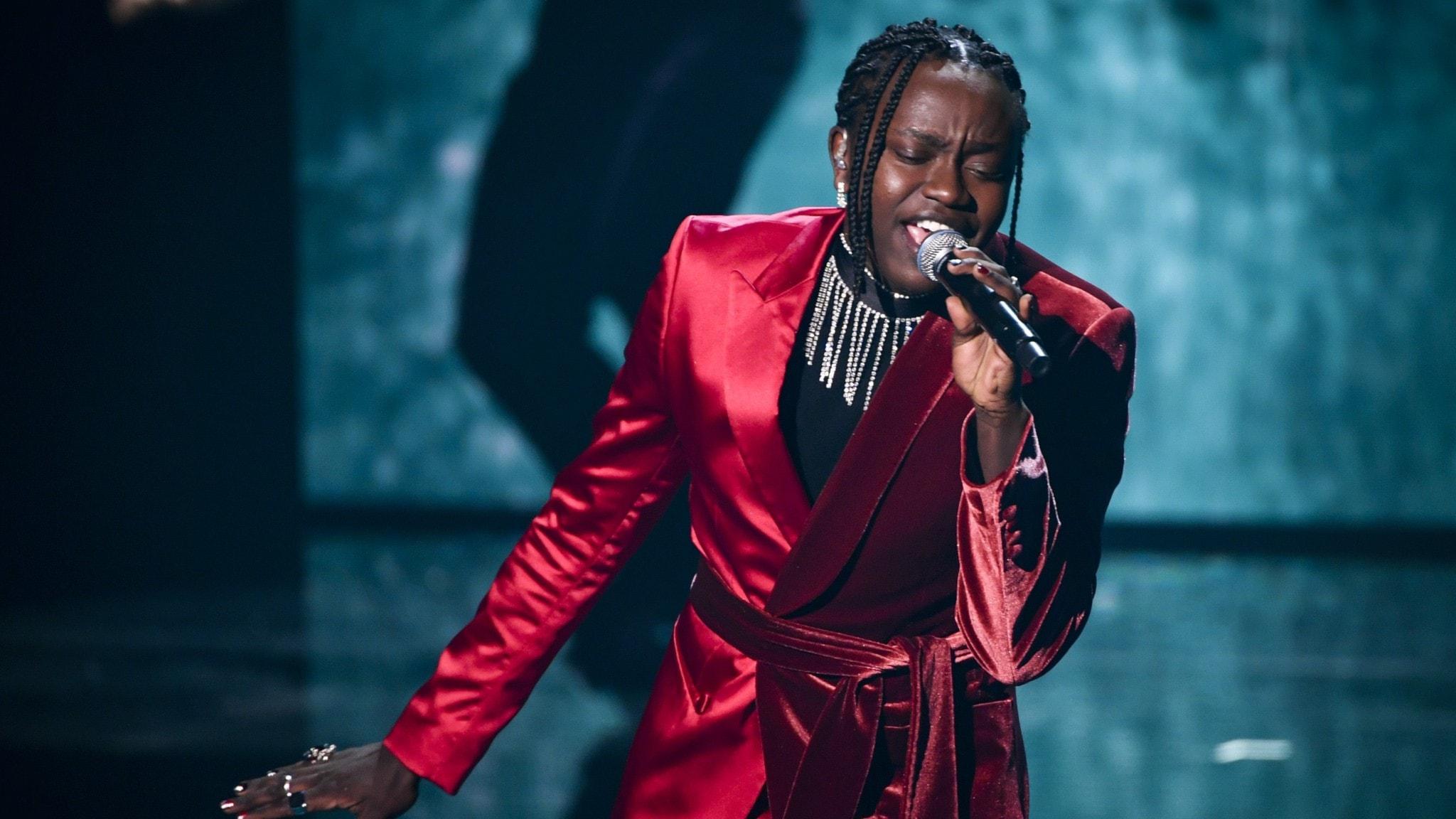 Artisten Tusse, klädd i röd, glansig kostym, på scen under melodifestivalens final.