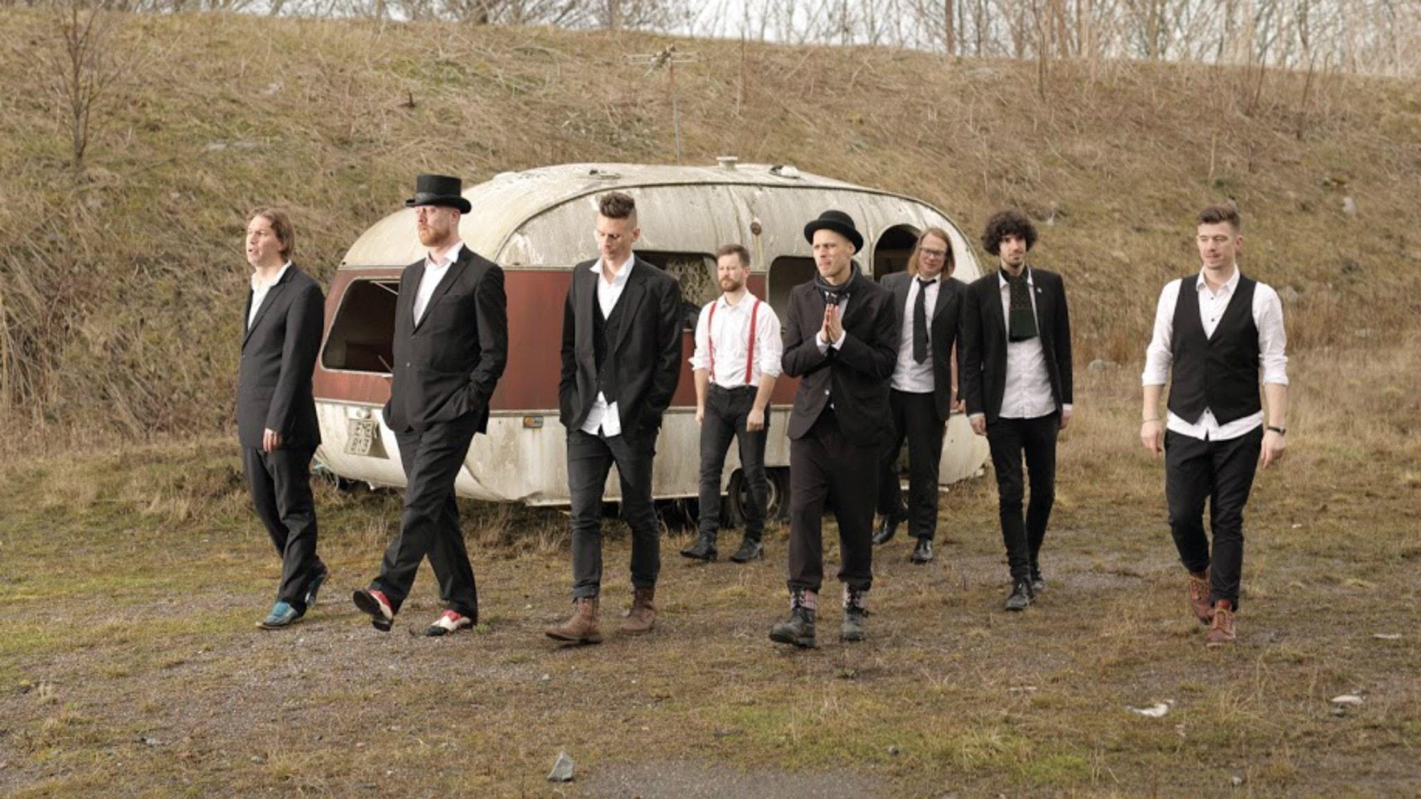 Åtta kostymklädda män går på en äng intill en gammal husvagn.