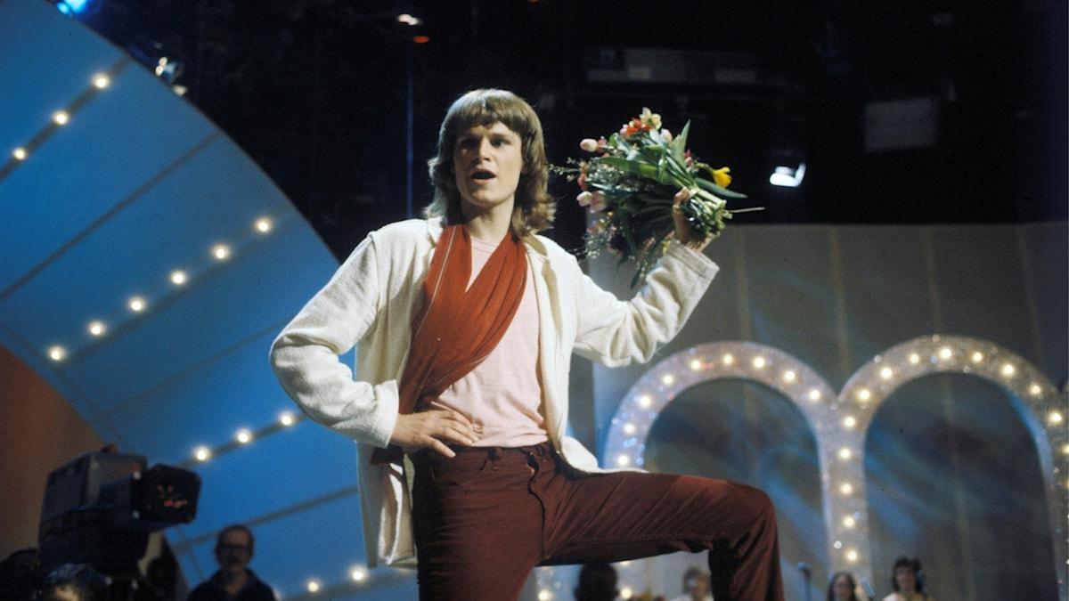 Ted Gärdestad håller i en blombukett.