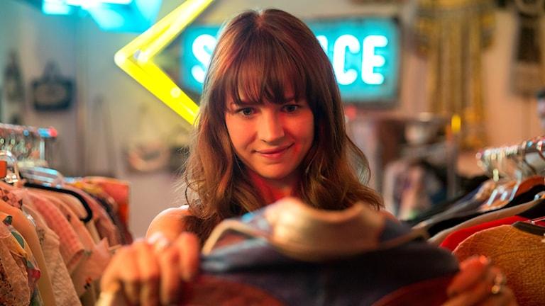 """Britt Robertssons karaktär Sophia kollar in en vintagejacka i tv-serien """"Girlboss"""""""