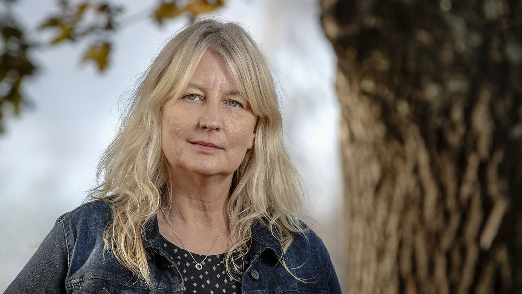 Ett porträtt av författaren Karin Smirnoff med ljust långt hår och klädd i jeansjacka vid en trädstam.
