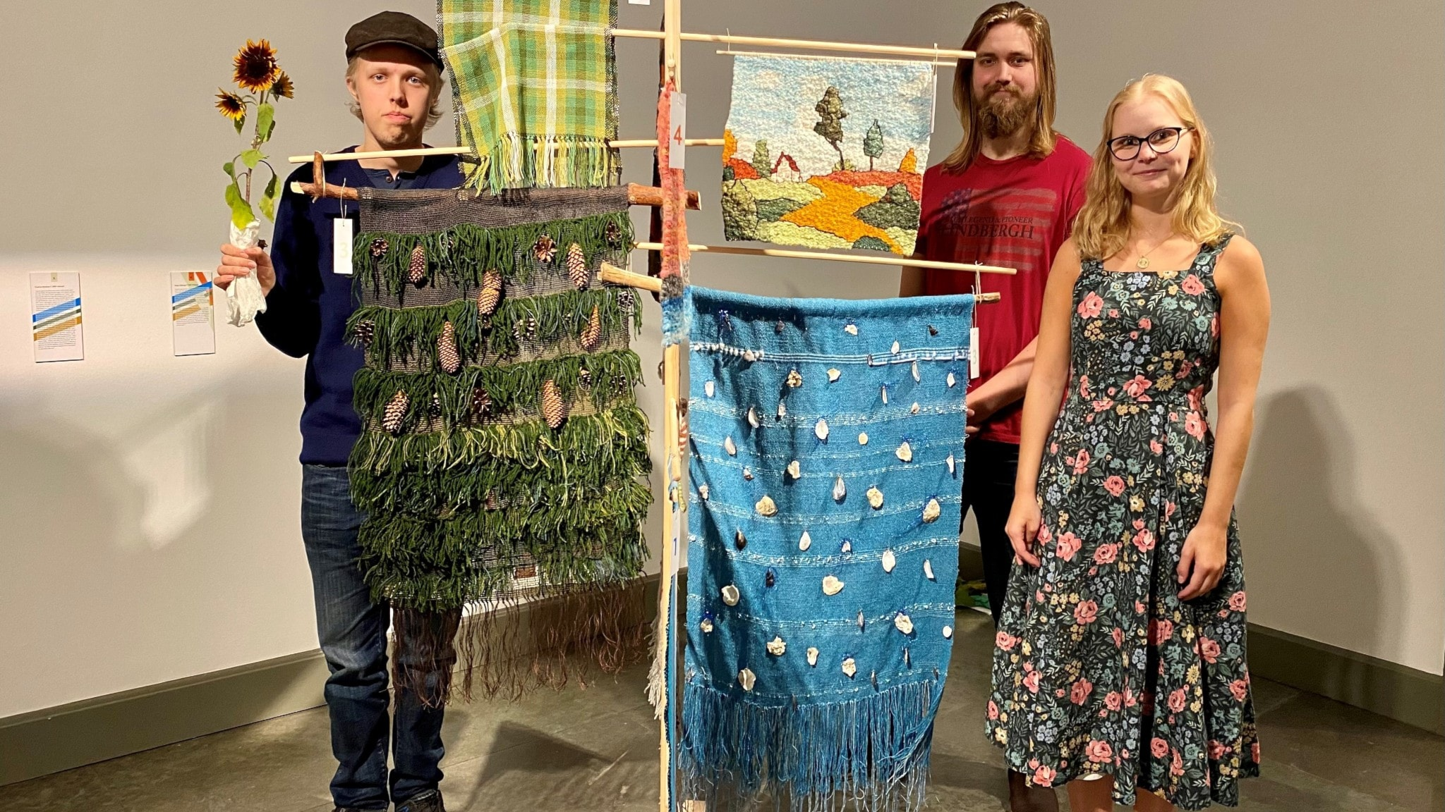 Tre personer står bredvid sina vävda klädesplagg och konstverk.