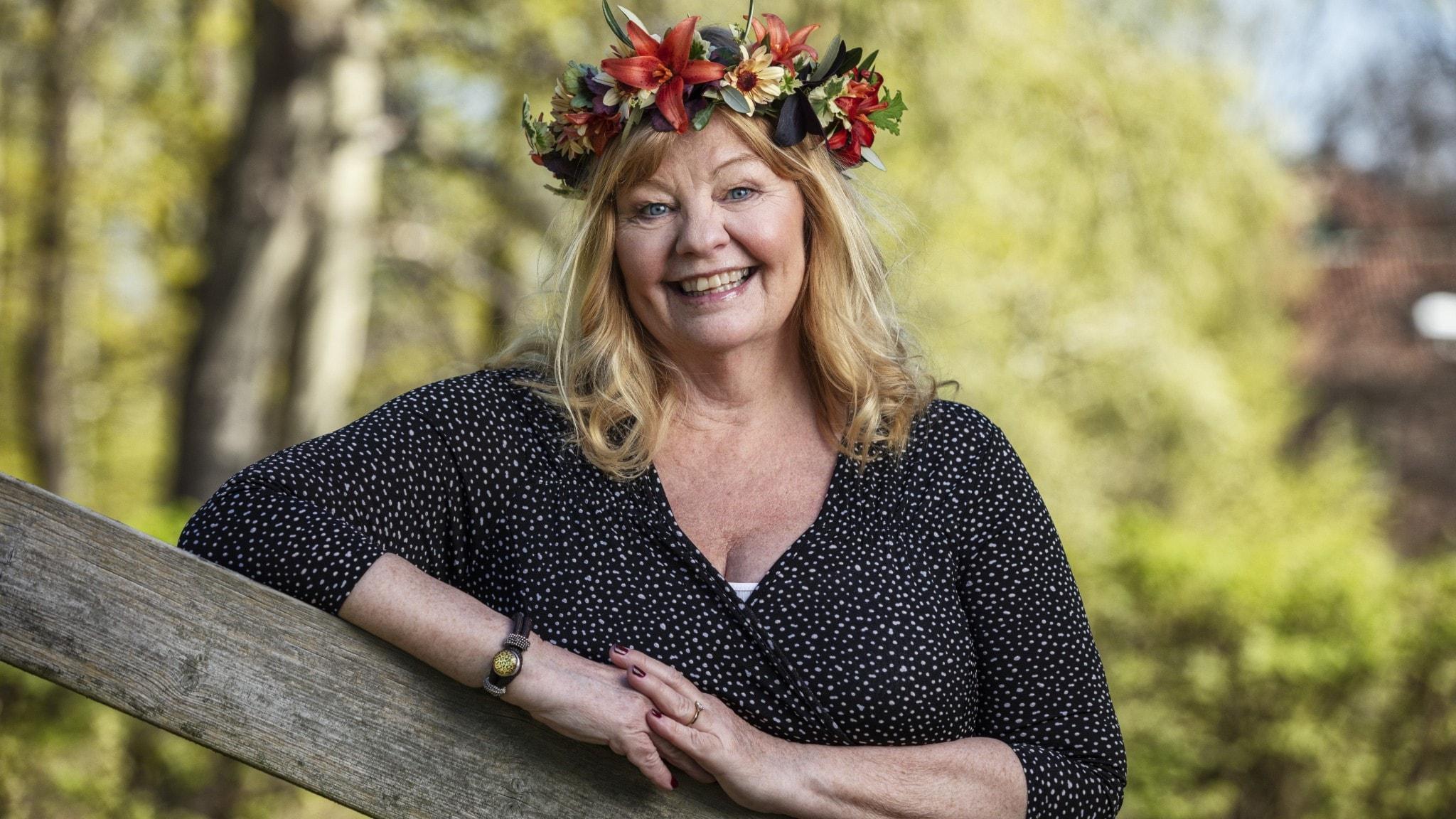 Inger Nilsson med blomsterkrans på huvudet.