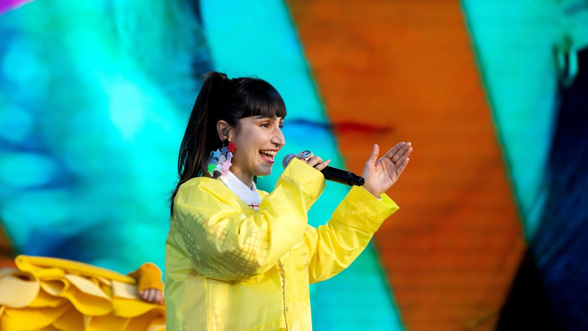 Kvinna i gul kavaj på scen