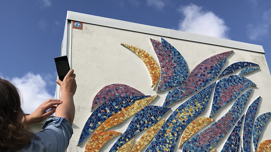 Karolina Peterson tar en bild på mosaikfiguren Space invader på Mjellby konstmuseum.