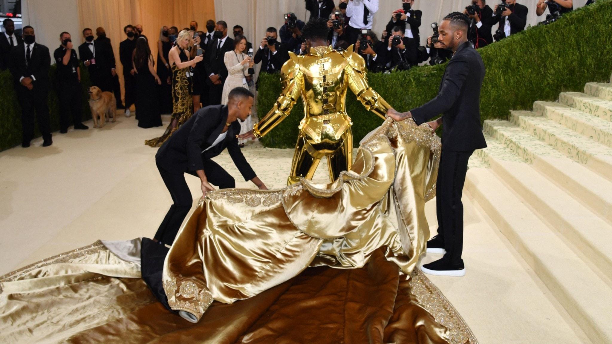 Lil Nas X sedd bakifrån får hjälp att ta av sig guldcape