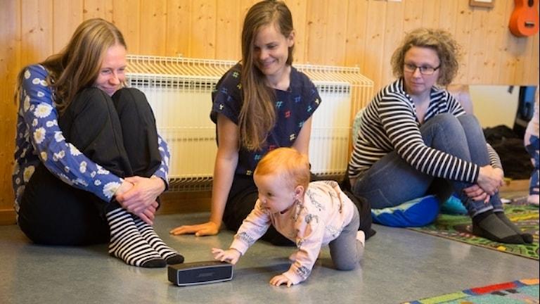 Felicia Snäll lyssnar på Bebispodden på Farstaängens öppna förskola tillsammans med poddens skapare Micaela Gustafsson, producent Emilia Traneborn och mamma Jessica Snäll.