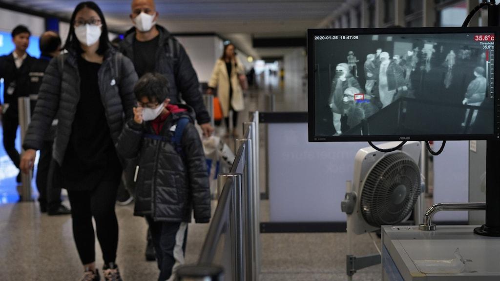 Personer med munskydd går igenom en kontroll på Hong Kongs flygplats.