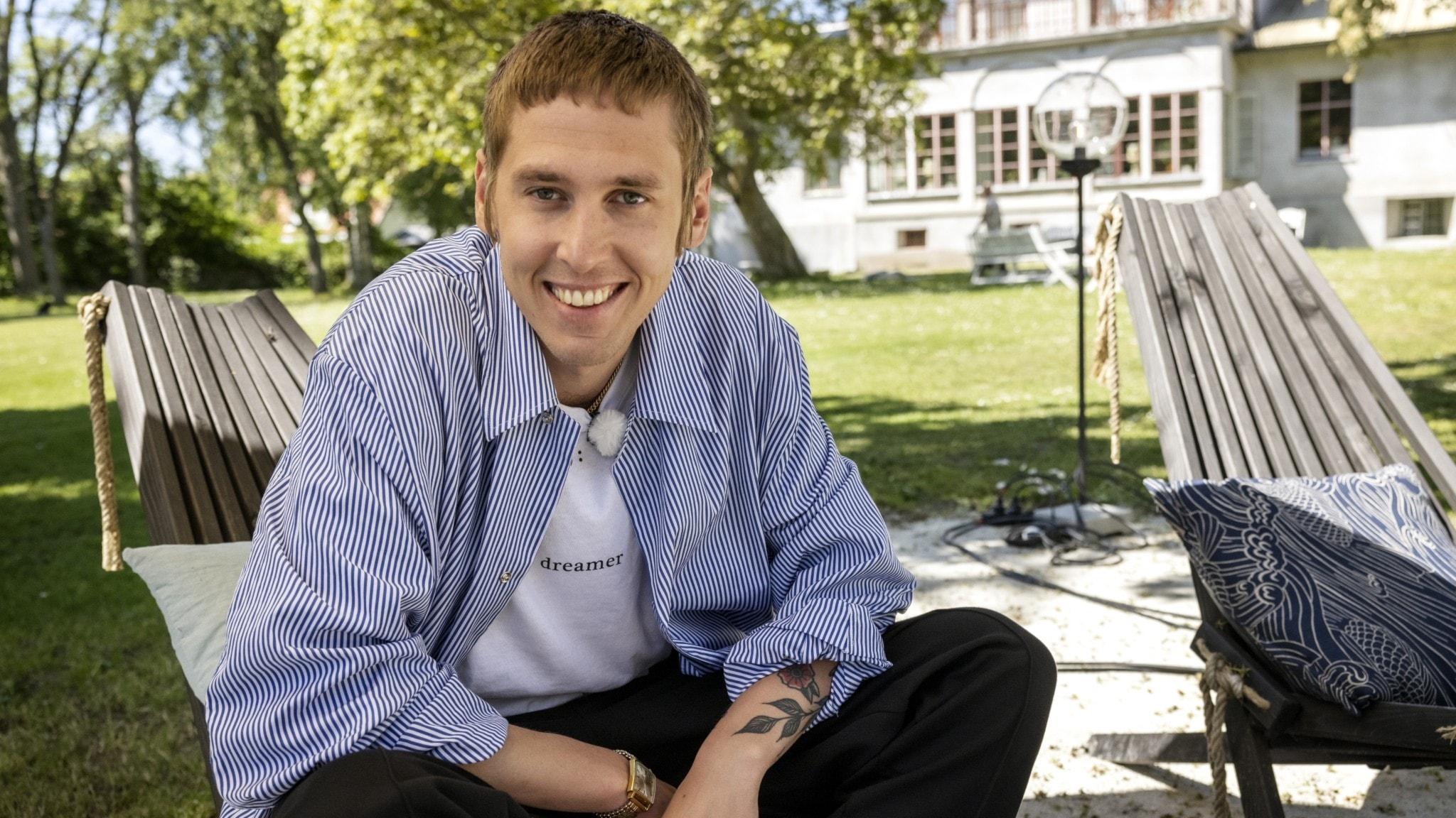 En leende ung man sitter i en solstol med uppknäppt skjorta och ser in i kameran.