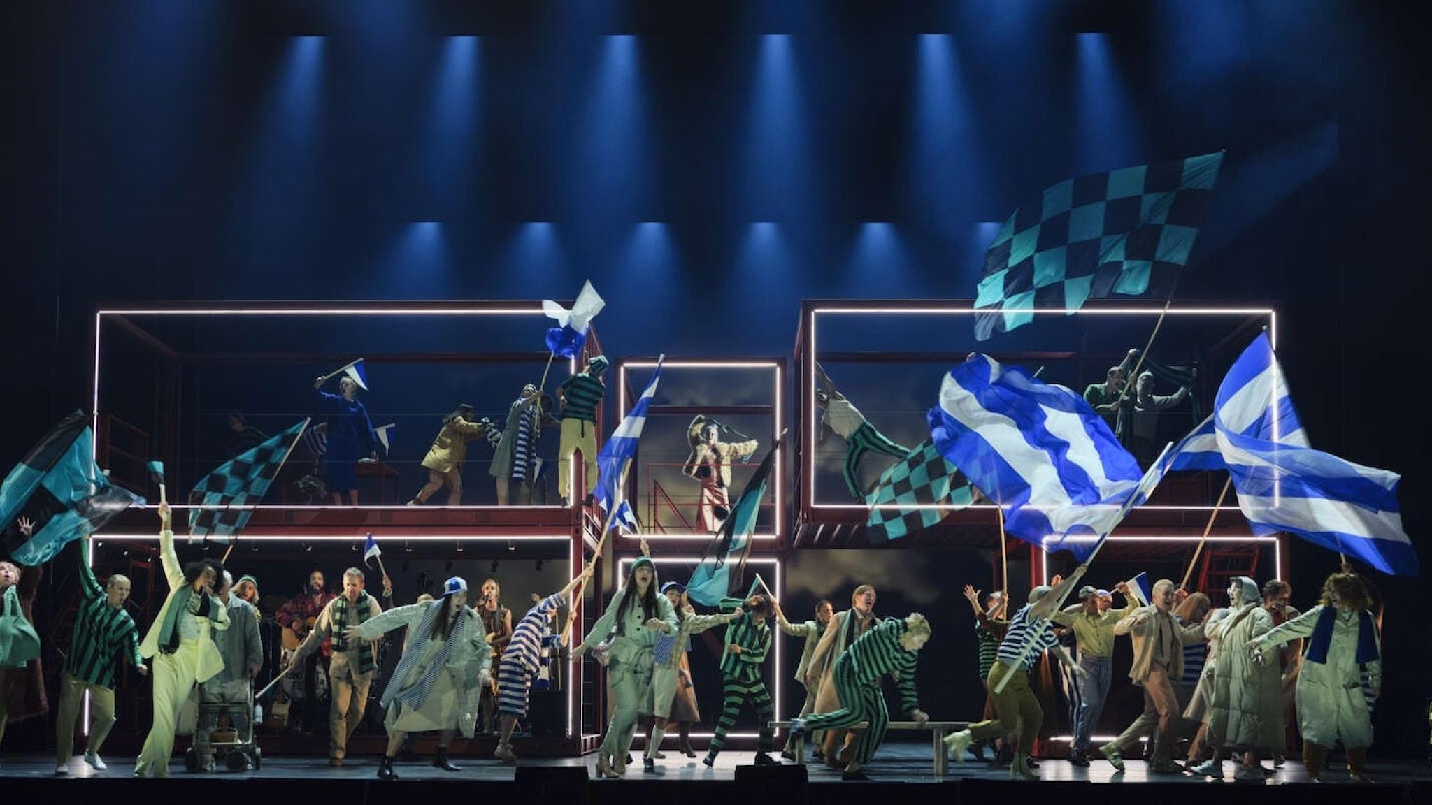 Sångare och dansare på scen med fotbollsflaggor