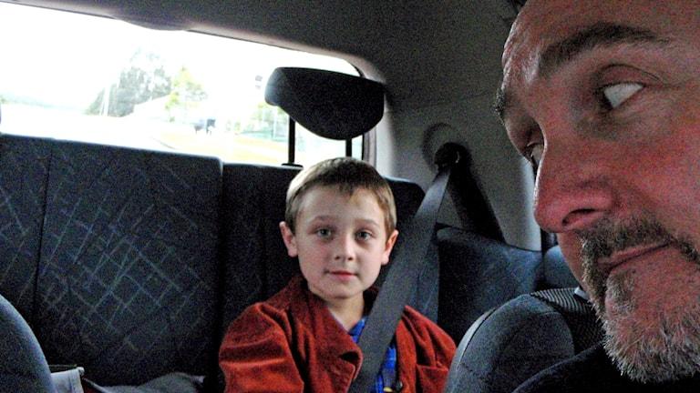 Man i förarsätet på en bil sneglar bak på sonen som sitter fastspänd i bilbältet i baksätet.