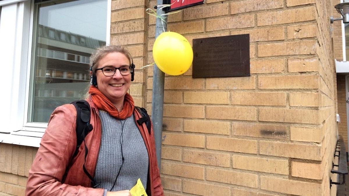 Pernilla Eskilsdotter har fäst en ballong på en stolpe bredvid plaketten på husväggen vid Nygatan 16 i Växjö som talar om att här föddes tonsättaren Karl-Birger Blomdahl 19 oktober 1916.