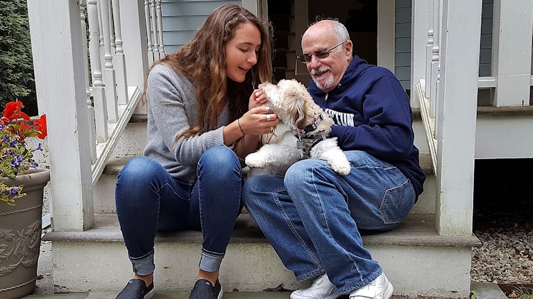 Grace Ellrodt and conductor David Zinman sit with Zinman's puppy Carlito