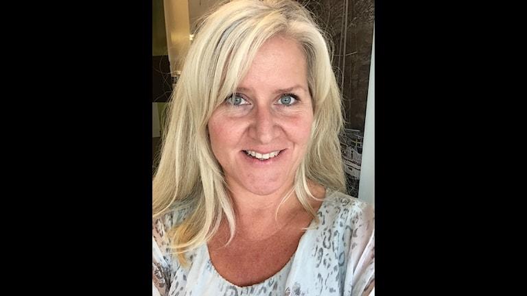 Porträtt av sara Holl Backman, hon har långt blont hår och en ljus blus.