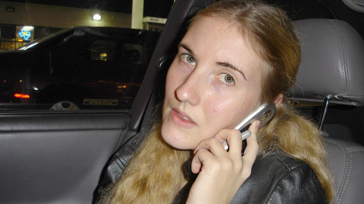 Kvinna i bil som pratar i mobiltelefon.