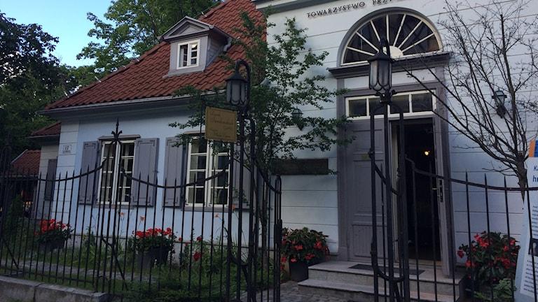 Utsidan av ett äldre hus med fönster, fönsterluckor, rabatt, träd och entrédörren på glänt.