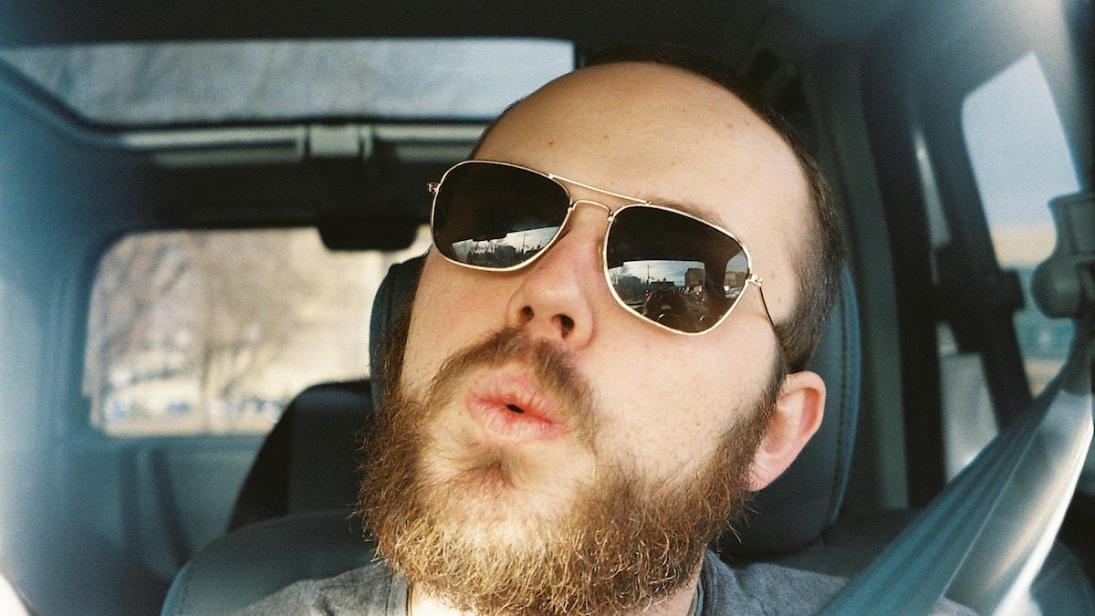 En skäggig man med solglasögon som sitter i en bil och visslar.