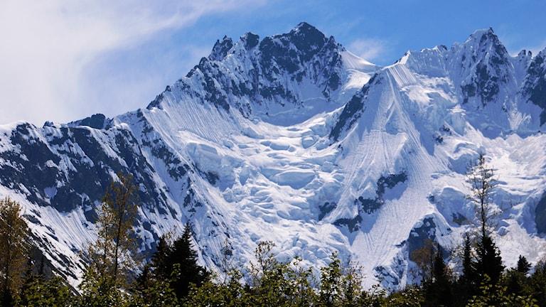 Solsken på snöiga berg i Alaska.