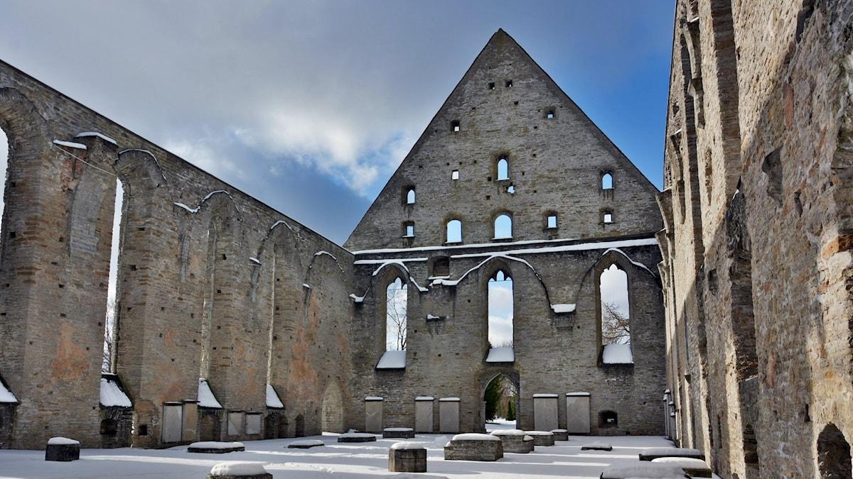 Ruinerna av Piritaklostret i Tallinn vintertid. Taket saknas och den blå himlen syns genom fönsteröppningarna. Snö på marken över rester av något som troligen varit pelare inne i klosterlokalen.