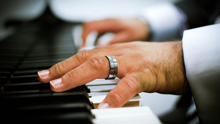 Närbild på en vänsterhand som tar ett ackord på ett piano.