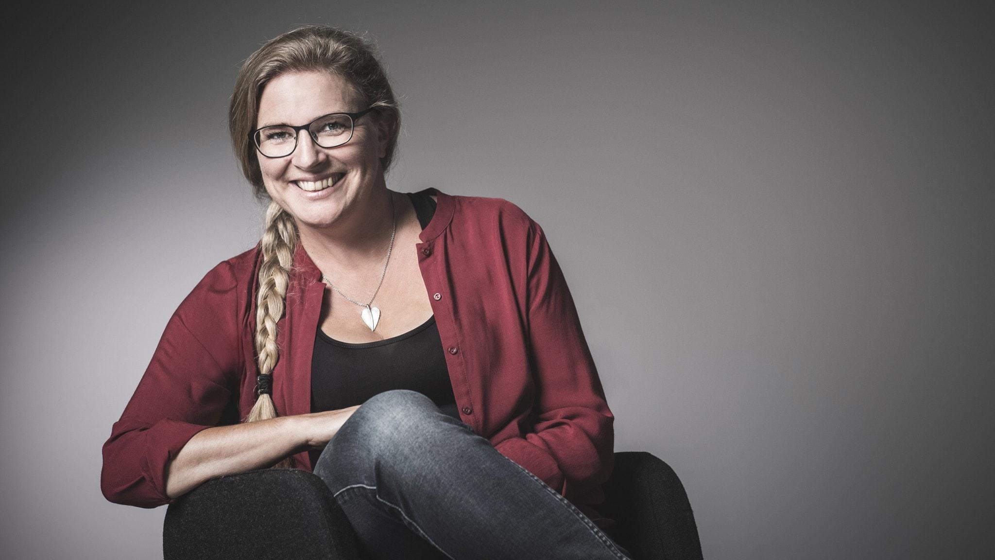 Pernilla Eskilsdotter sitter i en fåtölj och ler.