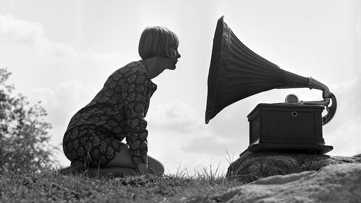Kvinna sitter på huk framför en gammal trattgrammofonspelare